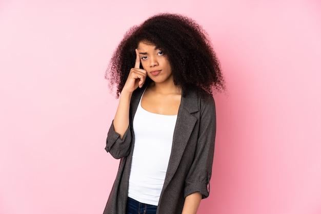 Молодая афро-американская женщина над стеной думая идея