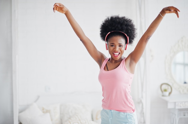 Young african american woman in pink singlet dancing and listen music on earphones at her white room.