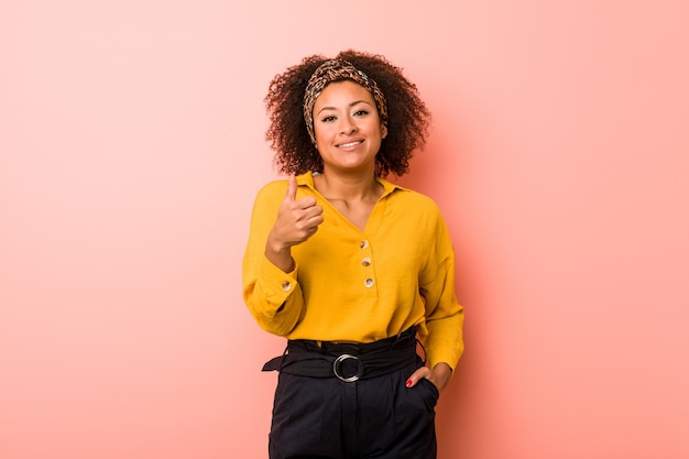 Young african american woman on pink smiling and raising thumb up