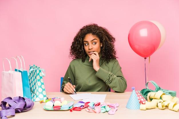 誕生日を計画している若いアフリカ系アメリカ人の女性は、コピースペースを見ている何かについて考えてリラックスしました。