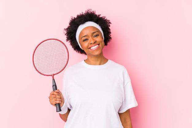 Молодая афро-американская женщина, играющая в бадминтон, изолировала счастливую, улыбающуюся и веселую.