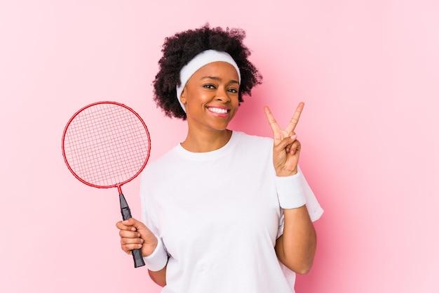 Молодая афро-американская женщина, играющая в бадминтон, изолирована, показывая номер два пальцами.