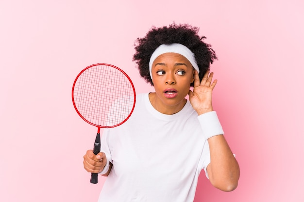 Young african american woman playing badminton isolated trying to listening a gossip.