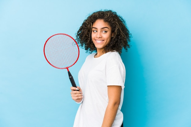 Молодая афро-американская женщина, играющая в бадминтон, выглядит улыбающейся, веселой и приятной.