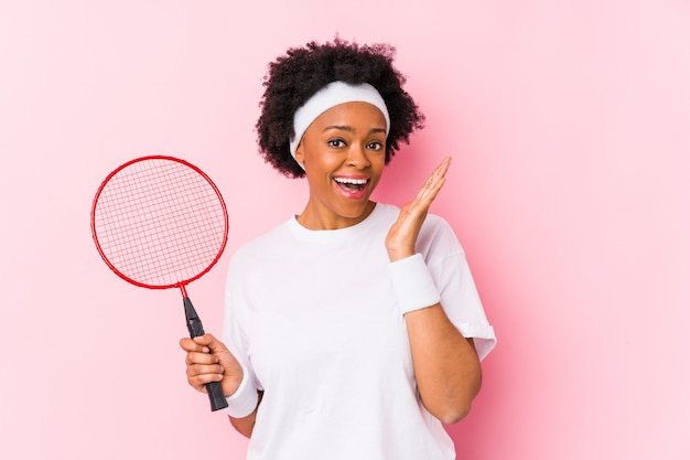 Young african american woman playing badminton surprised and shocked.