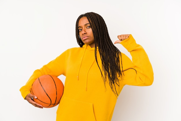 Young african american woman playing basketball isolated feels proud and self confident, example to follow.
