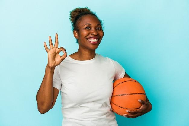 青の背景に分離されたバスケットボールをしている若いアフリカ系アメリカ人の女性は、陽気で自信を持って大丈夫なジェスチャーを示しています。