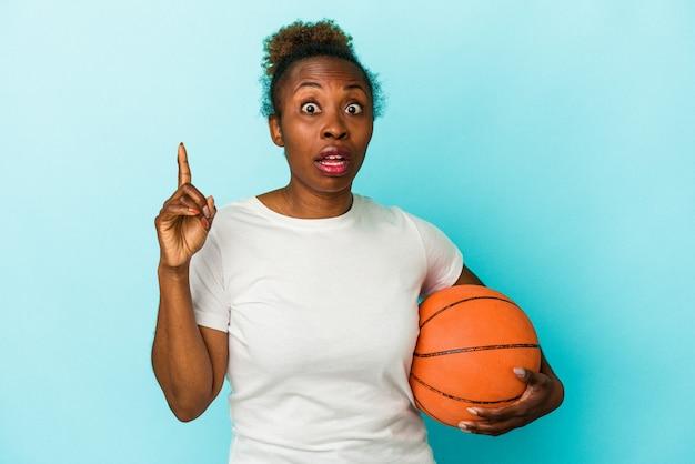 アイデア、インスピレーションの概念を持つ青い背景で隔離のバスケットボールをしている若いアフリカ系アメリカ人女性。