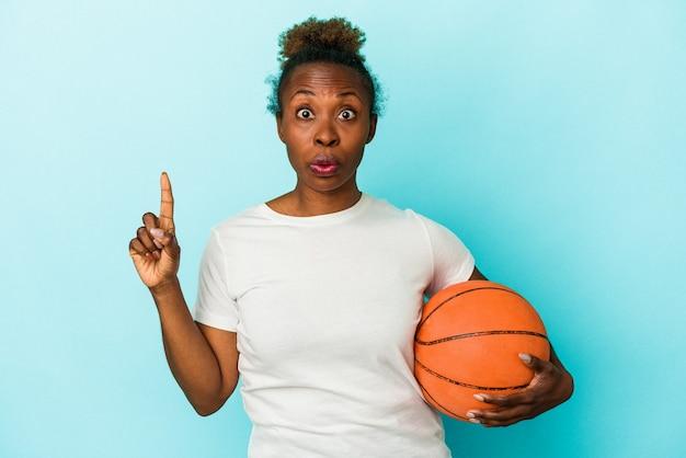 파란색 배경에 격리된 농구를 하는 젊은 아프리카계 미국인 여성은 훌륭한 아이디어, 창의성 개념을 가지고 있습니다.