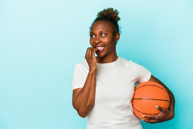 파란색 배경에 격리된 농구를 하는 젊은 아프리카계 미국인 여성은 복사 공간을 보고 있는 무언가에 대해 편안하게 생각했습니다.
