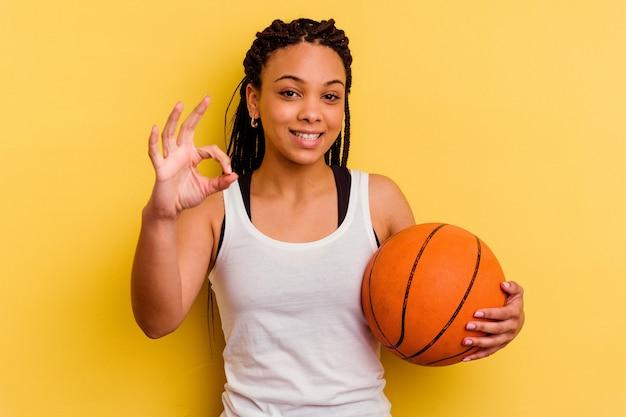 黄色の背景に分離されたバスケットボールをしている若いアフリカ系アメリカ人女性は、明るく自信を持って大丈夫なジェスチャーを示しています。
