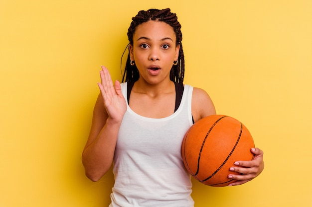 黄色の背景に分離されたバスケットボールをしている若いアフリカ系アメリカ人女性は驚いてショックを受けました。