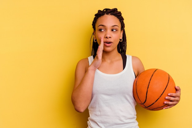 黄色で隔離されたバスケットボールをしている若いアフリカ系アメリカ人の女性は、秘密の熱いブレーキングニュースを言って、脇を見ています