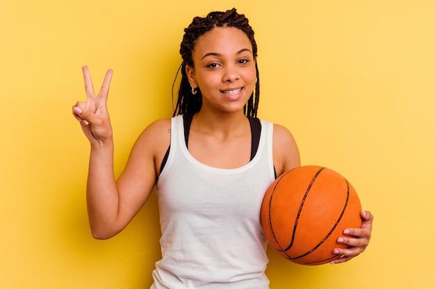 指で平和のシンボルを示す黄色の喜びとのんきに分離されたバスケットボールをしている若いアフリカ系アメリカ人の女性。