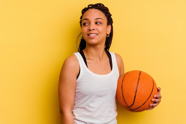 黄色で隔離されたバスケットボールをしている若いアフリカ系アメリカ人の女性は、笑顔、陽気で楽しい脇に見えます。