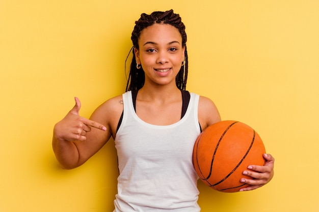 誇りと自信を持って、シャツのコピースペースを手で指している黄色の人に分離されたバスケットボールをしている若いアフリカ系アメリカ人女性