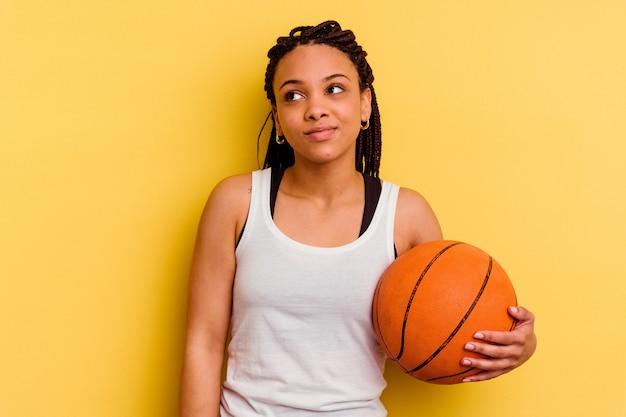 목표와 목적을 달성하는 꿈을 꾸고 노란색 벽에 고립 된 농구를하는 젊은 아프리카 계 미국인 여자
