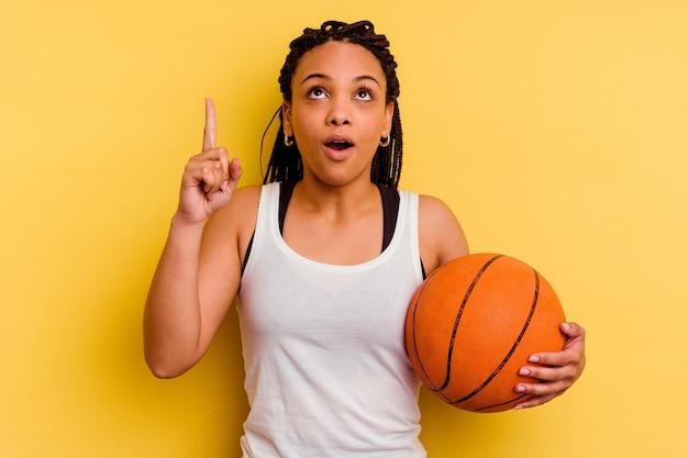 開いた口で逆さまを指している黄色の壁に分離されたバスケットボールをしている若いアフリカ系アメリカ人女性。