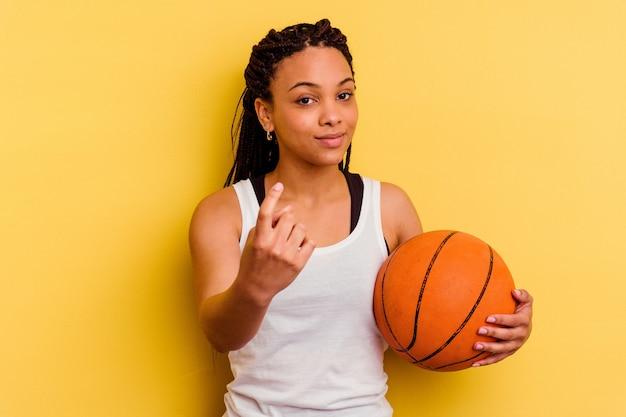 誘うようにあなたに指で指している黄色の壁に分離されたバスケットボールをしている若いアフリカ系アメリカ人女性が近づく