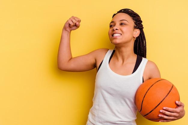 勝利の後に拳を上げる黄色の壁に分離されたバスケットボールをしている若いアフリカ系アメリカ人女性