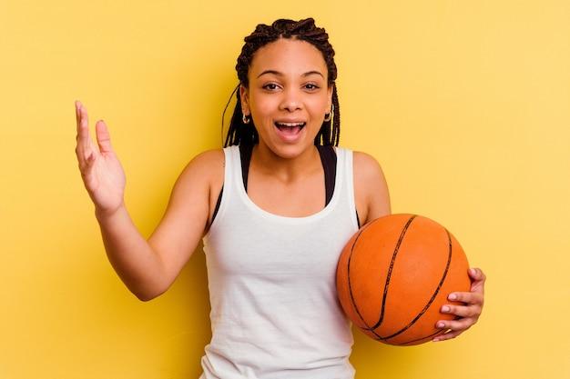 黄色の壁に隔離されたバスケットボールをしている若いアフリカ系アメリカ人の女性は、嬉しい驚きを受け取り、興奮し、手を上げます。