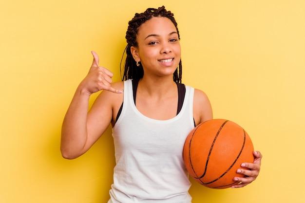 指で携帯電話の呼び出しジェスチャーを示す黄色の壁に分離されたバスケットボールをしている若いアフリカ系アメリカ人女性