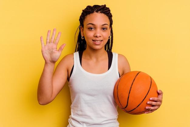 黄色の壁に隔離されたバスケットボールをしている若いアフリカ系アメリカ人の女性は、指で5番を示して陽気に笑っています。
