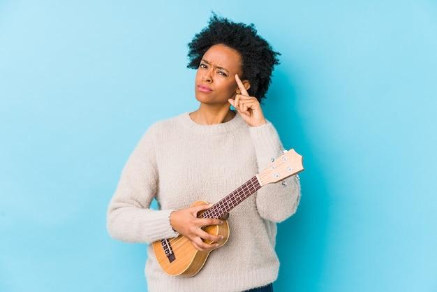 ウクレレを演奏する若いアフリカ系アメリカ人女性は、指で寺院を指して、考え、タスクに焦点を当てています。