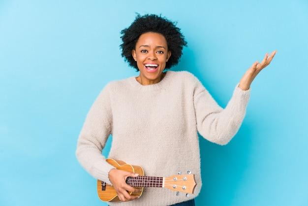 ウクレレを演奏する若いアフリカ系アメリカ人女性は、嬉しい驚きを受けて興奮し、手を上げて分離しました。