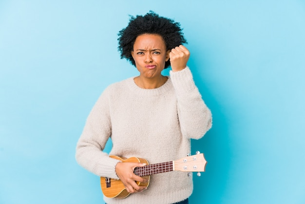 Young african american woman playing ukelele isolated showing fist  aggressive facial expression.