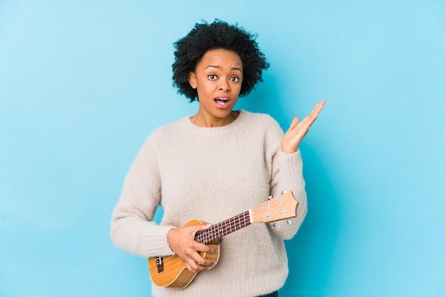 ウクレレを演奏若いアフリカ系アメリカ人女性は驚いてショックを受けて分離しました。
