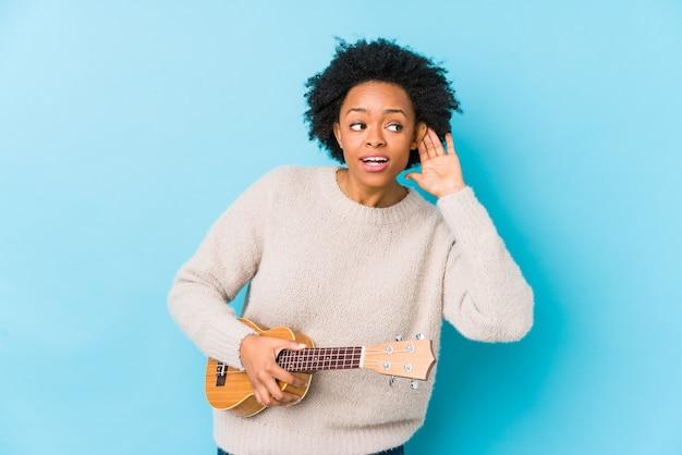 Молодая афро-американская женщина, играющая на укелеле, изолирована, пытаясь слушать сплетню.