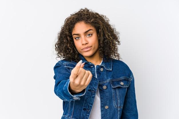 Молодая афро-американская женщина указывая пальцем на вас, как будто приглашая подойти ближе.