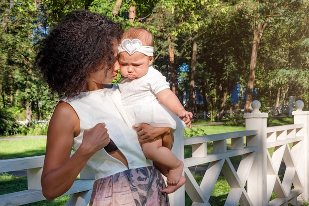 Young african american woman preparing for breastfeeding her baby in summer park.