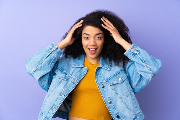 Young african american woman on purple wall with surprise expression