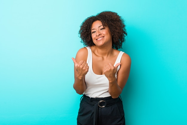 Young african american woman raising both thumbs up, smiling and confident.