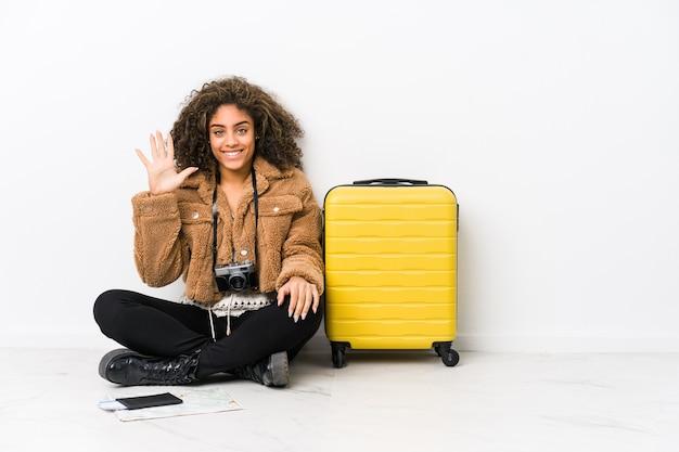 若いアフリカ系アメリカ人女性が指で陽気な表示数5を笑顔旅行の準備ができています。