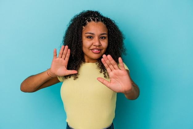 Молодая афро-американская женщина отвергая кого-то, показывая жест отвращения.