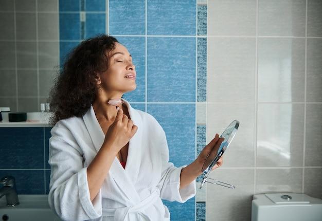 목을 부드럽게 하고 옥석 롤러 마사지기로 림프 배수 마사지를 하는 동안 휴식을 취하는 젊은 아프리카계 미국인 여성