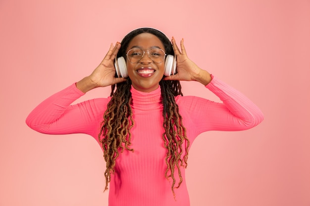 Young african-american woman's portrait isolated on pink background.