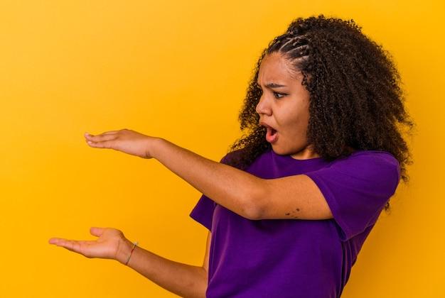 若いアフリカ系アメリカ人の女性は、手でサイズを表示することにショックを受け、驚いています