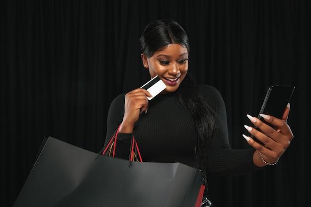 Молодая афро-американская женщина, делающая покупки с красочными пакетами на черной стене. Бесплатные Фотографии