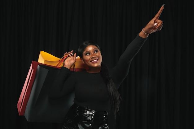 Молодая афро-американская женщина, делающая покупки с красочными пакетами на черном