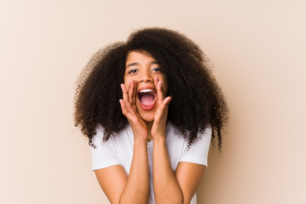 Young african american woman shouting excited to front.