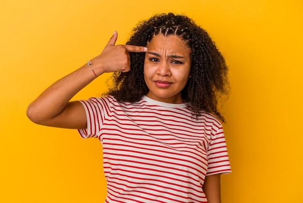 Молодая афро-американская женщина, показывающая жест разочарования с указательным пальцем.