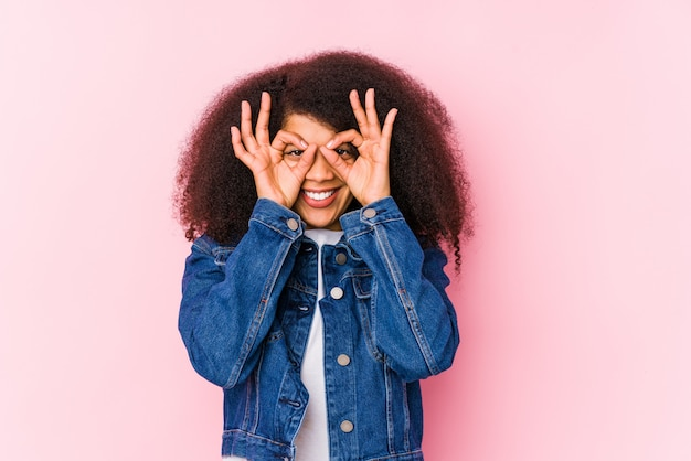 Young african american woman showing okay sign over eyes