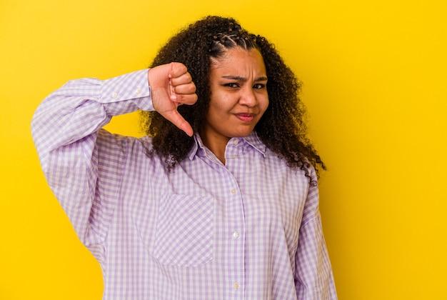 親指を下に向けて嫌悪感を表現している若いアフリカ系アメリカ人女性。