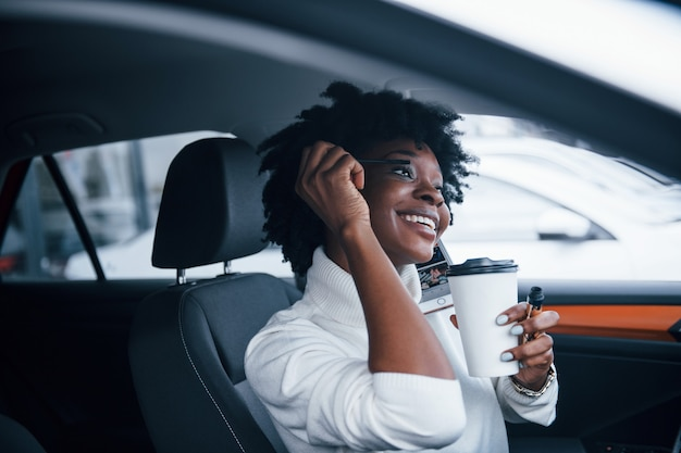 Young african american woman sits inside of new modern car.