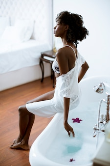 Young african american woman sitting on the bathtub in the bathroom