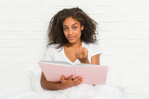 Young african american woman sitting on the bed studying pointing with finger at you as if inviting come closer.